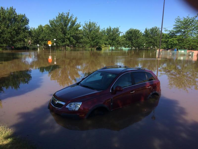 A car sits in the flooded parking lot of Midland's downtown farmers' market.