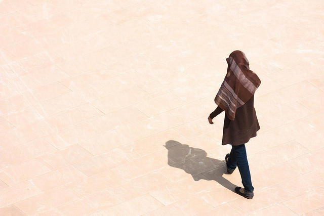 Woman with head covering walking away