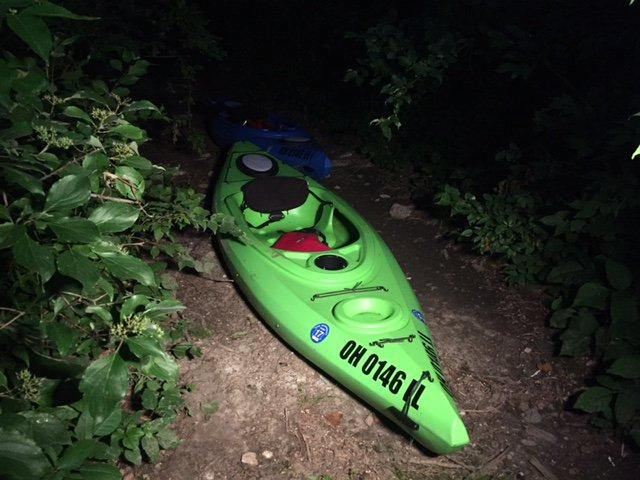 A picture of two kayaks, one red, one green, on a trail in the woods