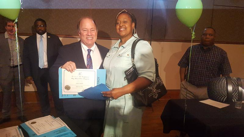 Mayor Mike Duggan handing Kiya Snapp the deed to her house after she completed the occupied buy back program