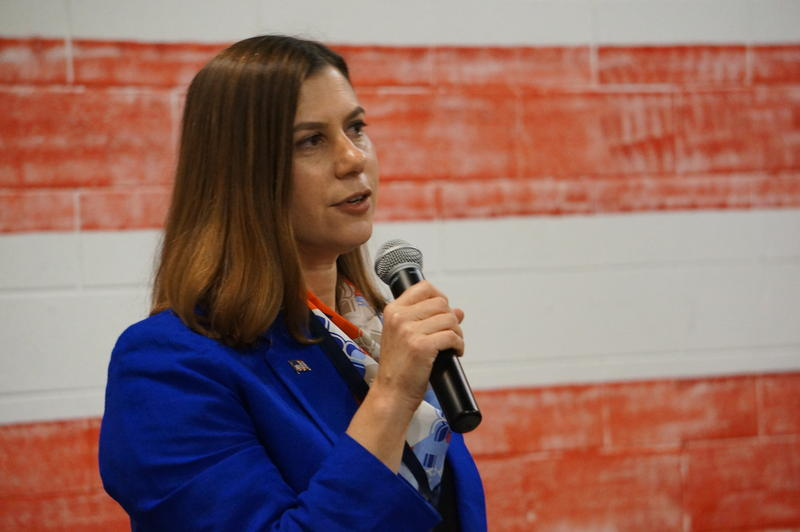 Elissa Slotkin, in blue short holding a microphone, stands in front of a red-and-white striped background.