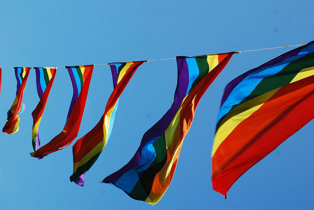 A string of rainbow flags against a blue sky