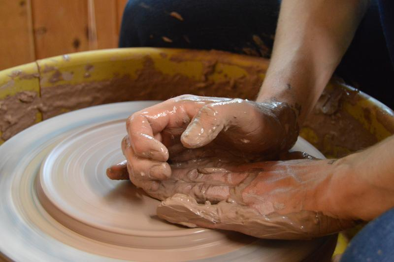 Kate Lewis finding the balance between pushing the clay and being gentle with it to shape it with her hands.