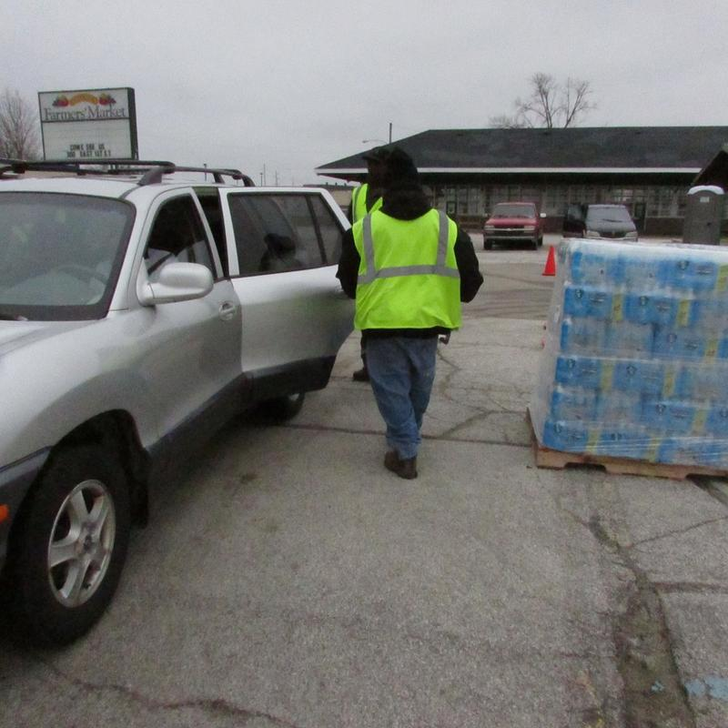 A worker in a bright-green vest loads bottled water into a silver SUV.
