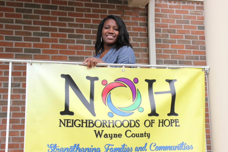 Taisha standing behind a sign that says neighborhoods of hope