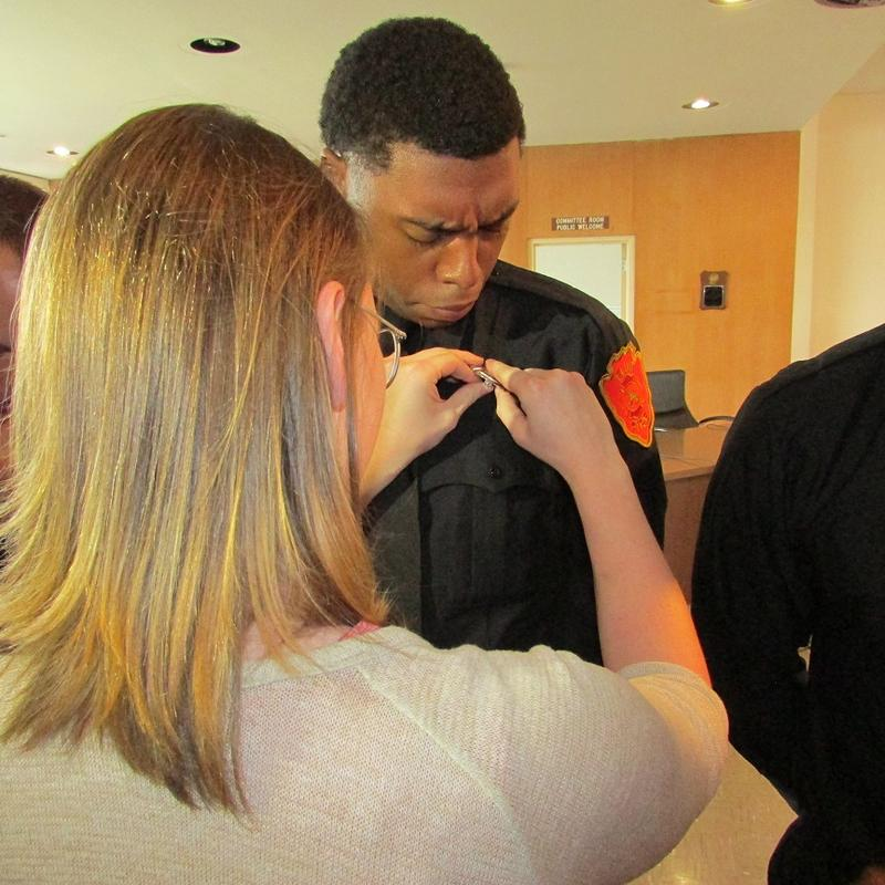 Friends and family members pinned badges on Flint's newest firefighters at ceremonies Friday at city hall
