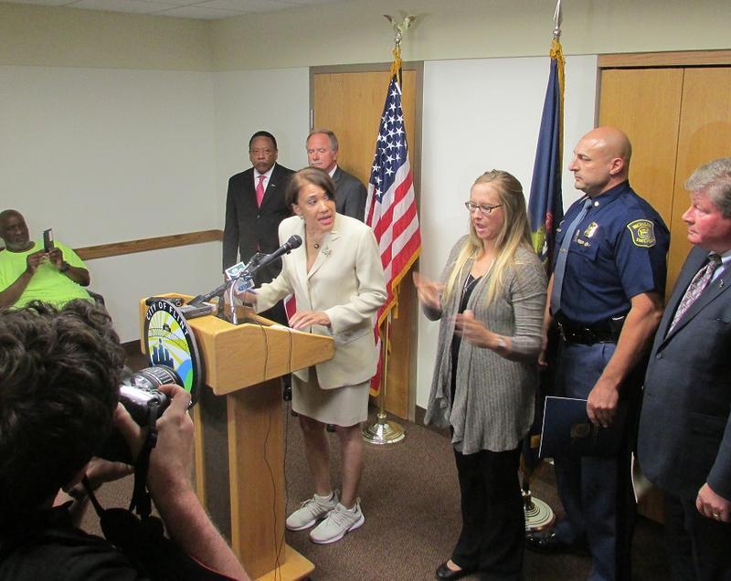 Flint Mayor Karen Weaver (at podium) announces plans to close 5 of 9 bottled water distribution sites in Flint