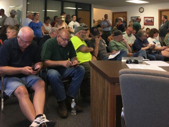 Kalkaska residents wait during a closed meeting session before public comment.