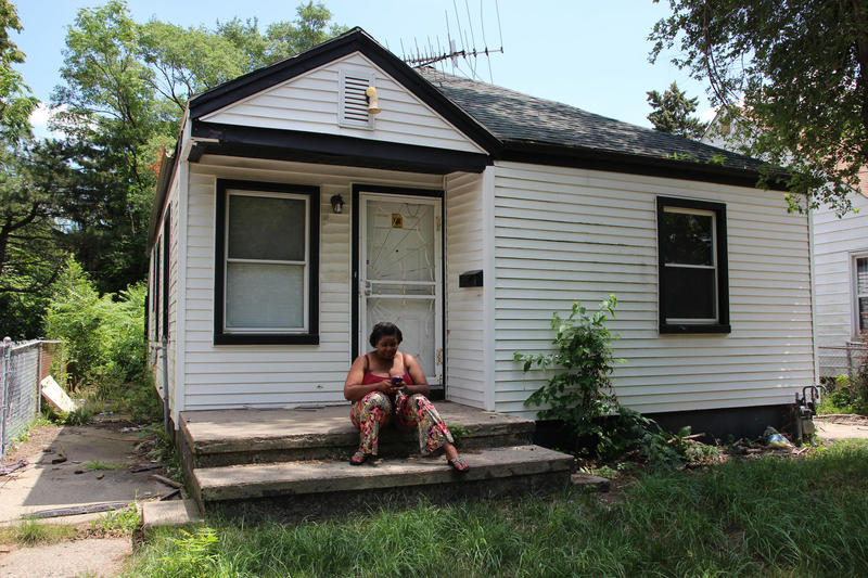 Keeria Myles sits on the front porch of her small white bungalow