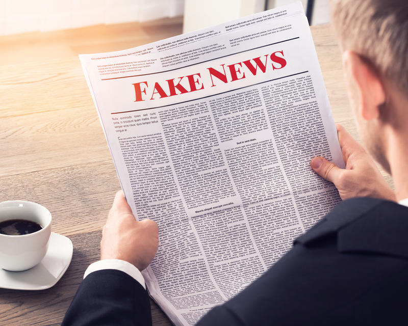 man reading newspaper with fake news written on it