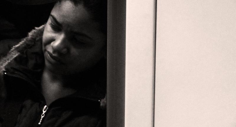 african american woman leaning against door frame