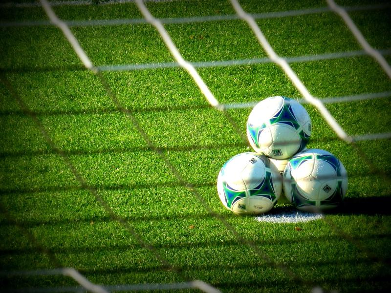 Three soccer balls sitting on a field, photographed through the net.