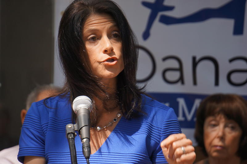 Dana Nessel, wearing blue, speaks into a microphone.
