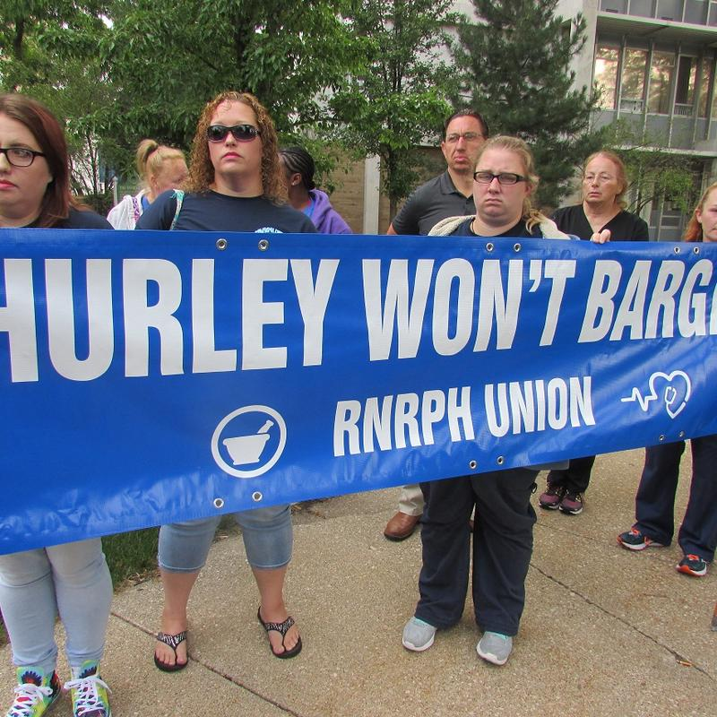 nurses holding banner that says hurley won't bargain