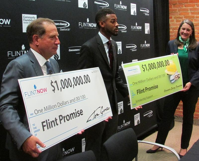 Palace Entertainment Vice Chairman Arn Tellem (left) and CMS President Patti Poppe (right) hand $1 million checks to Community Foundation President Isaiah Oliver.