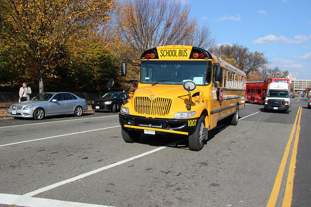 A yellow school bus driving down the road