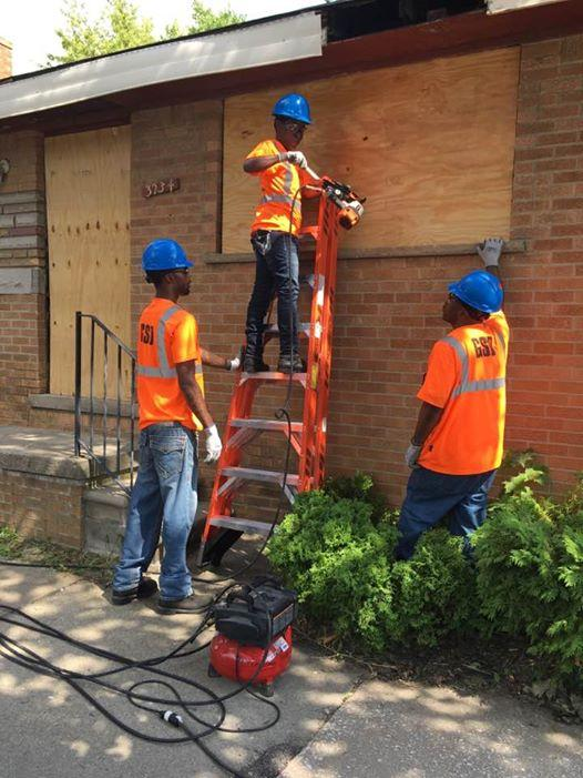 Workers board up a vacant home in southwest Detroit.