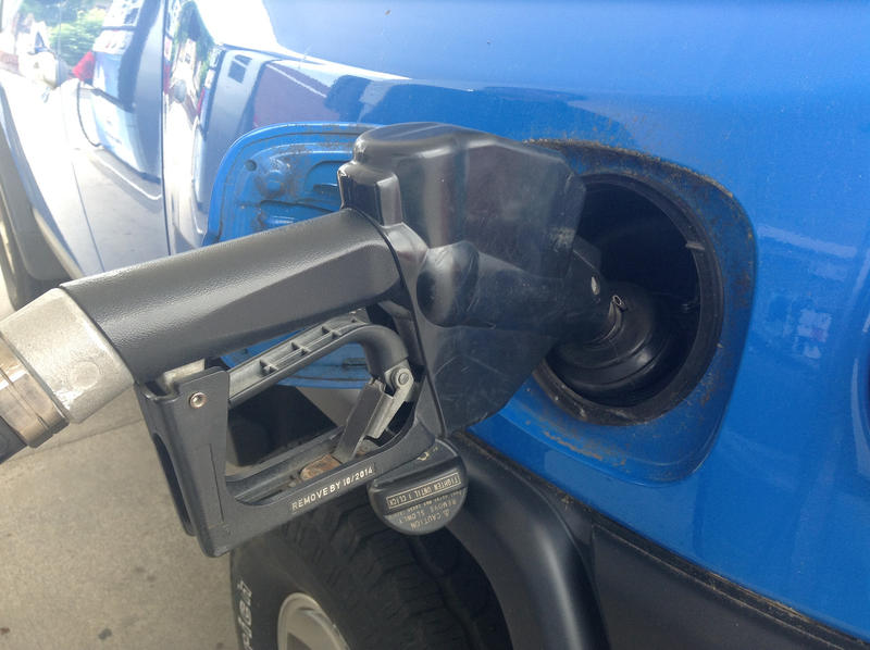 blue car fueling up at gas pump