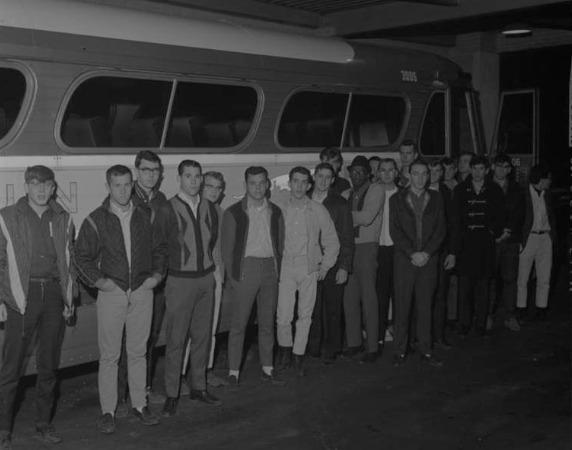 row of young men in front of bus