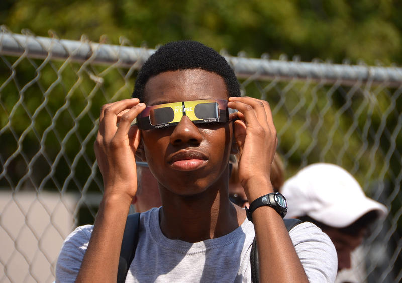 A boy wears special glasses to view the eclipse