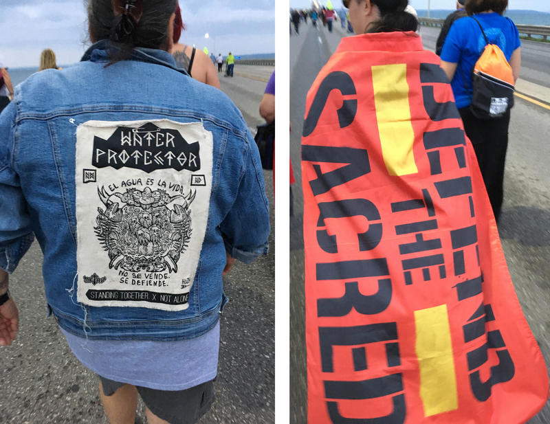 "Women walk wearing banners that say ""Water Protector"" and ""Defend the Sacred"""
