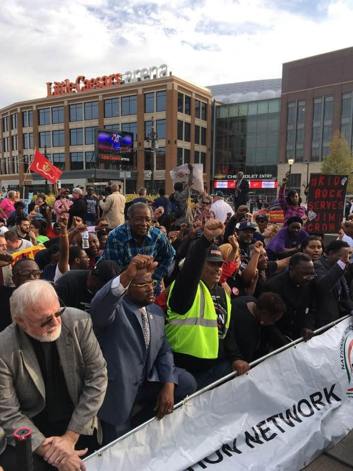 Protesters kneel while singing the national anthem in front of Little Caesar's Arena.