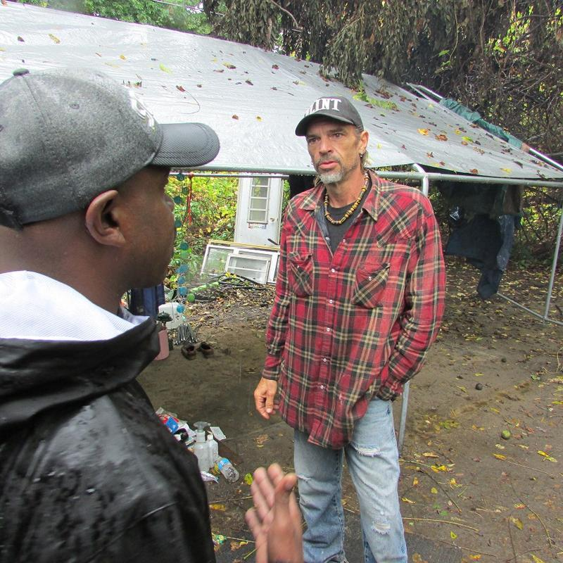 """Camp Promise resident Tim Robbins (right) told Flint City Councilman Wantwaz Davis the camp is about """"Peace, Love and Unity,"""" though he also admits to conflicts with people who want their neighborhood park back to the way it was."""