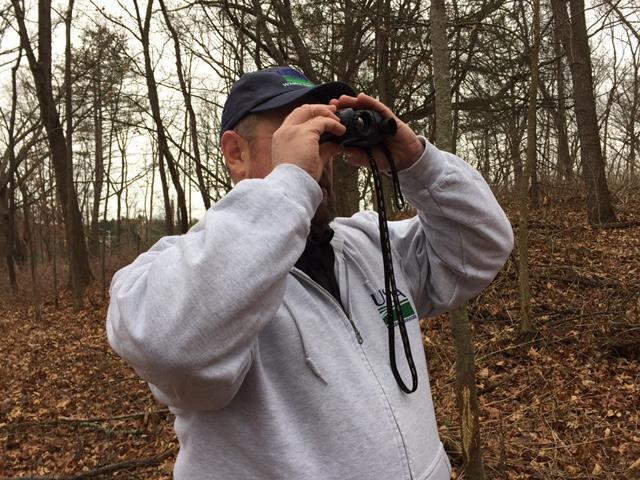 Anthony Duffiney, a supervisor in the USDA-APHIS Wildlife Services Program, peers through a FLIR device (Forward Looking Infrared) in a wood in the city of Ann Arbor