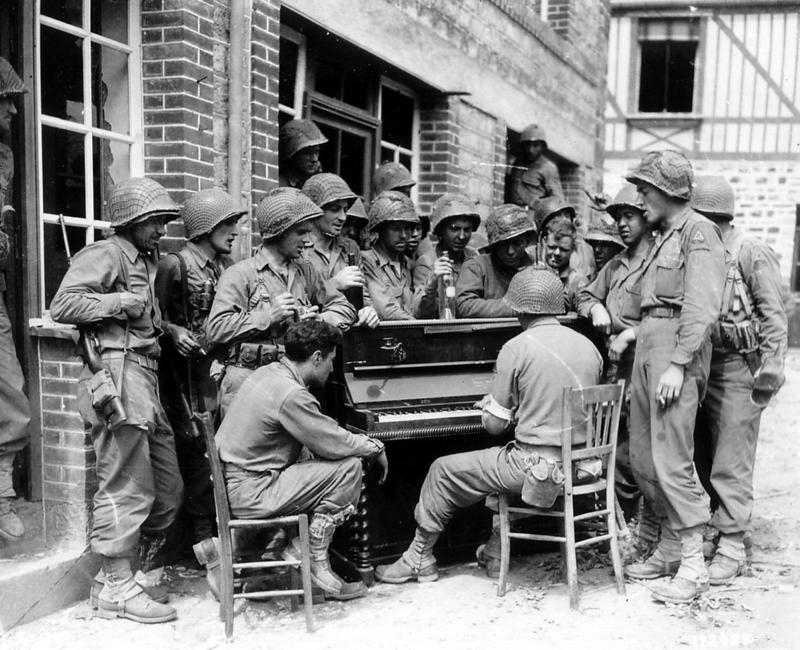 A groups of soldiers gather around a Steinway piano during WWII. The pianos were painted according to the military branch: olive drab for the Army and blue or gray for the Navy.