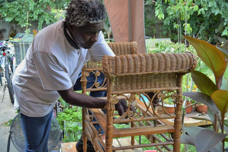 Babacar Lo is removing a damaged seat bottom from wicker furniture.