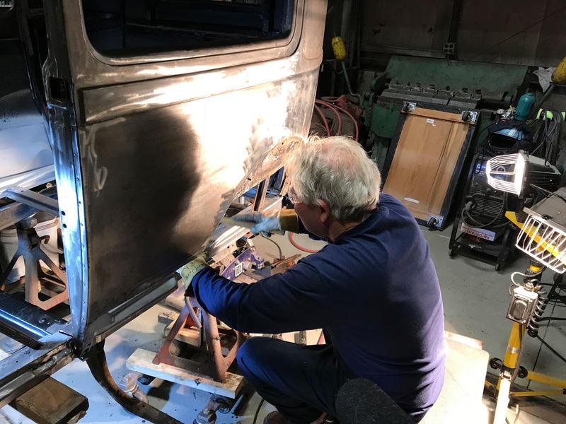 man welding antique car