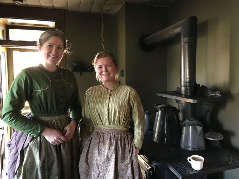 women in 1800s period clothing in front of coal-burning stove