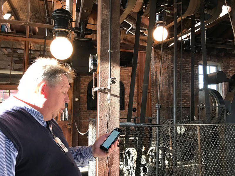 man looking at phone inside factory building