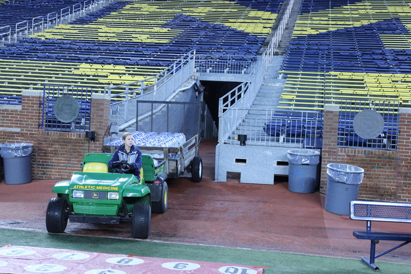 A stadium staff member delivers jugs of water to the sidelines about five hours before kickoff. Michigan Stadium has only one tunnel, so traffic can tricky before and during games.