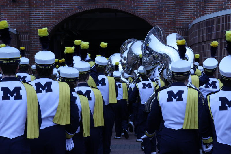 The Michigan Marching Band, 400-plus members strong, is longer than the tunnel into the stadium. The tail end of the group is almost in the parking lot.