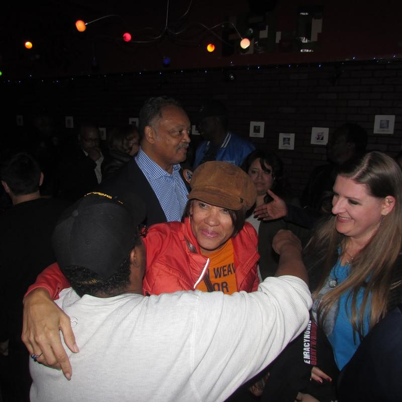 Flint Mayor Karen Weaver hugs a supporter as she enters her victory party, escorted by Rev. Jesse Jackson