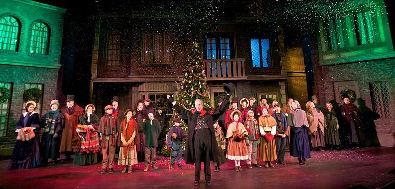 Thomas D. Mahard as Ebenezer Scrooge and the company of A Christmas Carol.