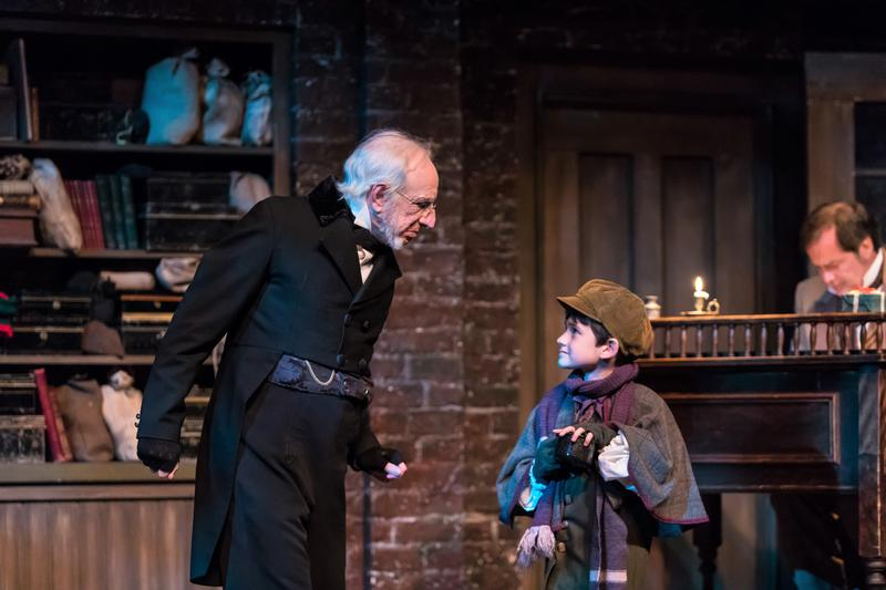 Thomas D. Mahard as Ebenezer Scrooge and Ethan Sharp as The Boy Caroller.