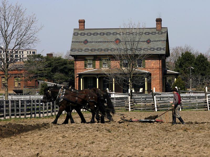 horses plowing a field in front of Firestone Farm