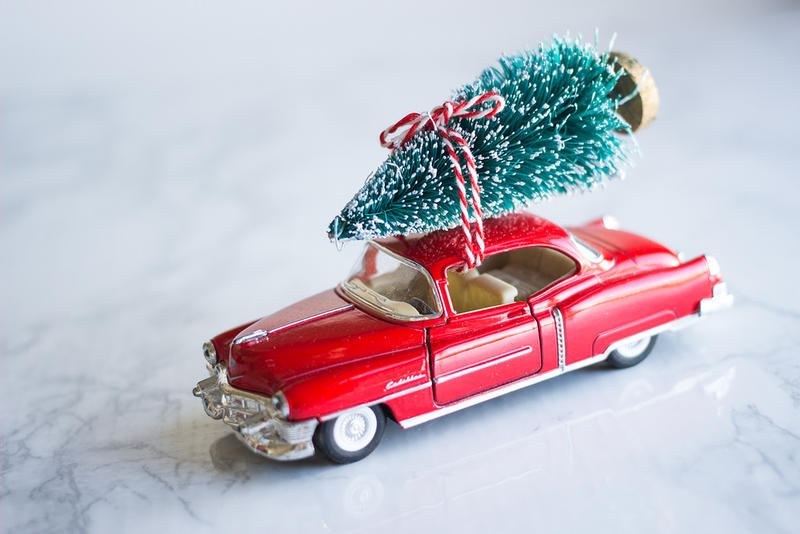Toy car with Christmas tree tied to roof