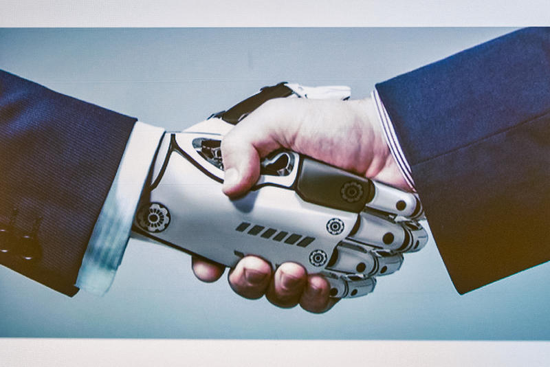 painting of robot hand and human hand in a handshake