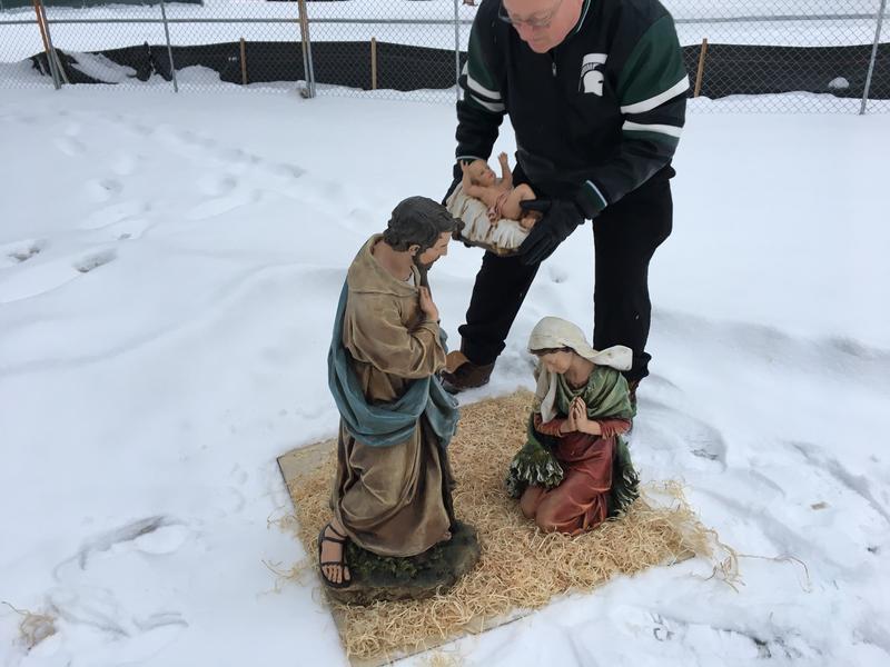 Jones holding baby Jesus near nativity scene