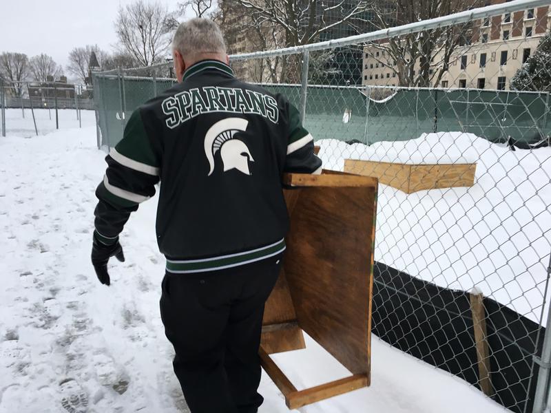 Jones in MSU jacket carrying wooden platform