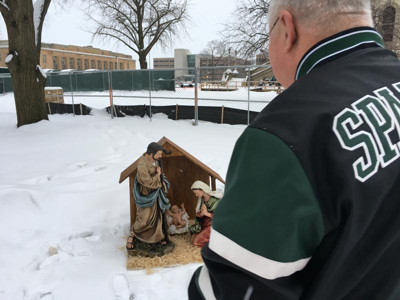 Jones standing in front of nativity display