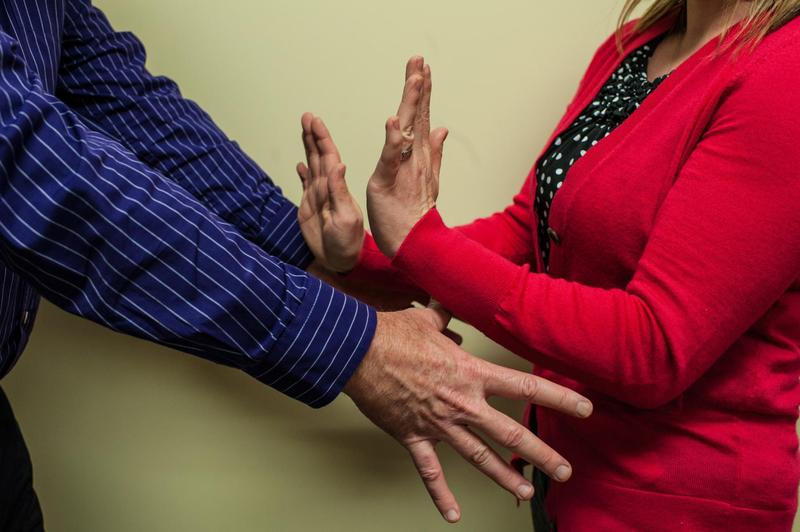 man's hands reaching toward woman's waist while she holds up her hands to stop him
