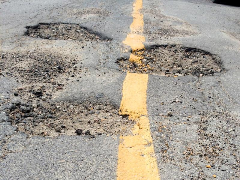 Multiple potholes along a concrete road.
