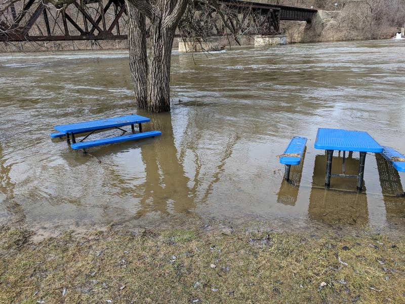 Picnic tables next to the Muskegon River surrounded by flood water