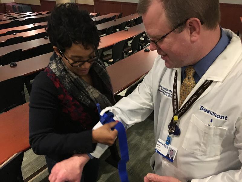 State Rep. LaTanya Garrett (D-Detroit) practices using a tourniquet on Dr. Allan Lamb, trauma medical director for Beaumont Trenton.
