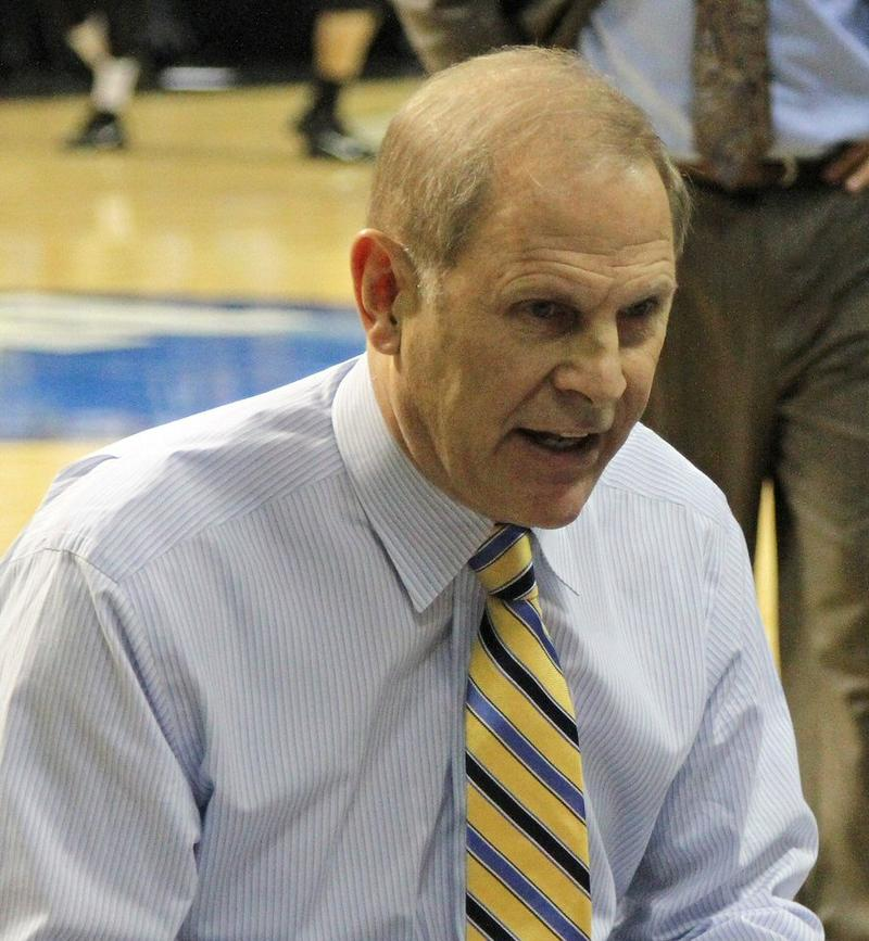 Michigan men's basketball coach John Beilein seated courtside