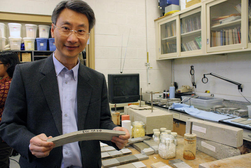 Victor Li stands with a sample of his self-healing concrete.
